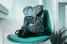 backpack and camera in a green office chair