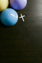 Silver cross on wooden table with colorful plastic Easter eggs.