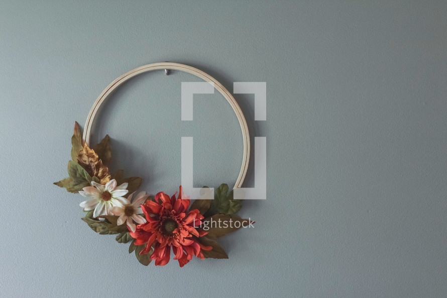fall wreath with artificial fall flowers hanging on a wall