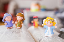 toy Bible figures on the pages of a Bible