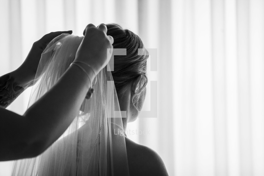 putting a veil on a bride