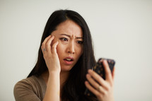 a woman reacting to something she saw on a cellphone screen