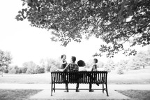 family sitting on a park bench
