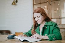 a woman sitting reading a Bible in a green blazer