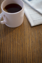 A cup of coffee next to a newspaper on a wooden table.
