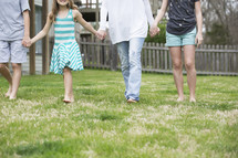 family walking holding hands outdoors