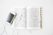 A cell phone and ear phones on an open Bible.