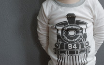 A child wearing a shirt with a train on the front.