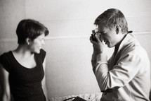 a man taking a picture of a woman with his camera