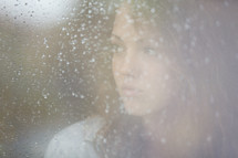 Woman looking out a frosted window pane.