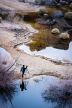 photographer with a tripod photographing nature