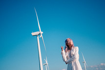 woman standing beside wind turbines
