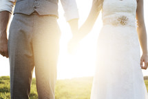 Newly married bride and groom holding hands under intense sunlight.