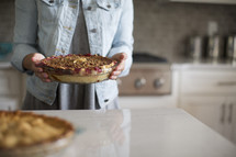 a woman holding a cherry pie in a kitchen.