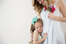 a little girl giving her mom a hug.