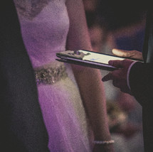 wedding rings presented to the bride and groom on an iPad