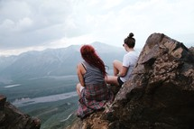 women sitting on rocks on the edge of a mountain