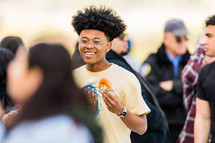 A smiling young man eating a donut in a group of people.