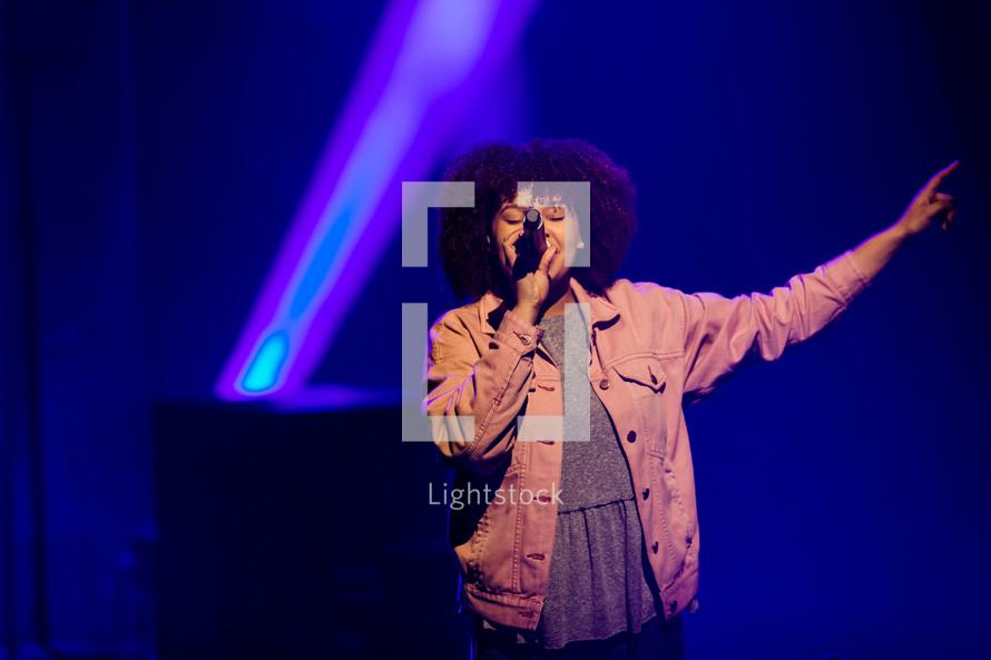 Singer under stage lights.