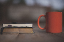 A Bible, notebook and orange mug of coffee