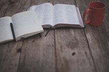 An open Bible and notebook next to an orange coffee mug
