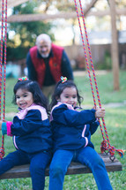 A grandfather pushing his granddaughters on a swing