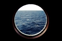 view of the ocean out a porthole window