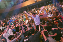 standing with raised hands at a worship service