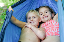 Smiling boy and girl in a blue hammock.
