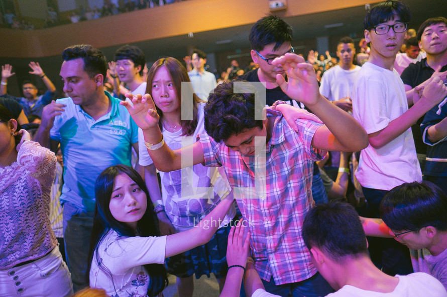 placing hands on another in prayer