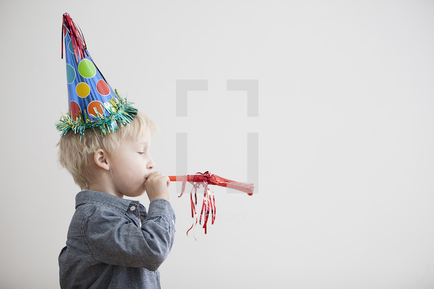 A toddler boy wearing a party hat.