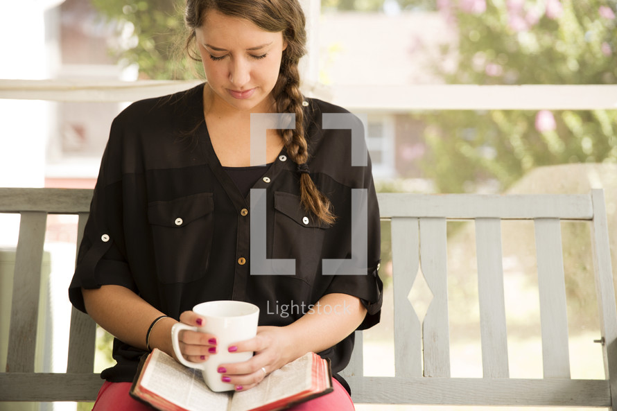 woman praying sitting on a porch swing with a Bible and coffee mug