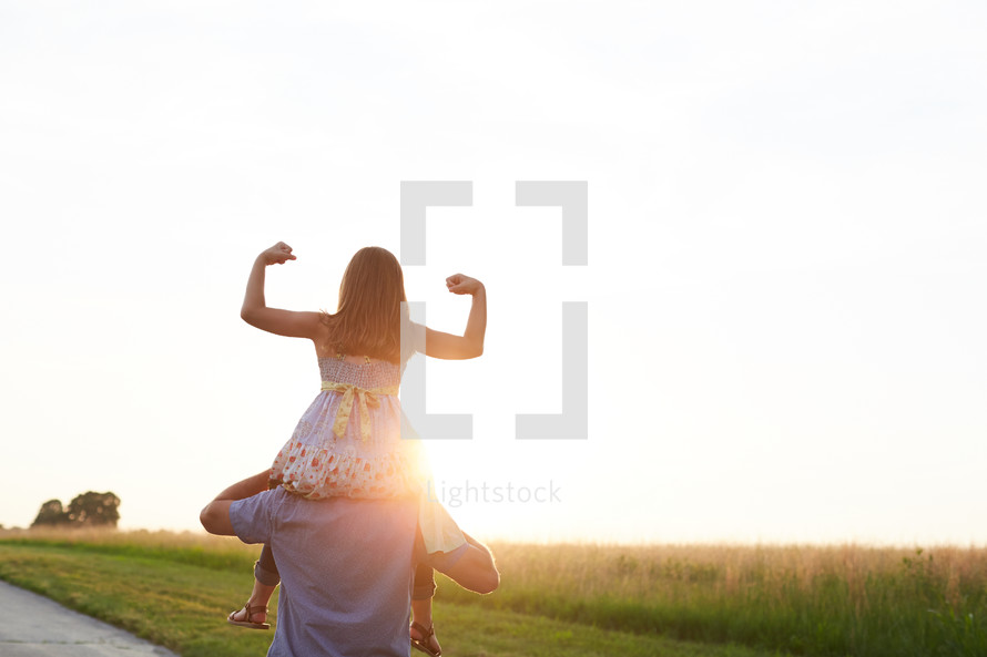 a daughter on her father's shoulders showing her muscles