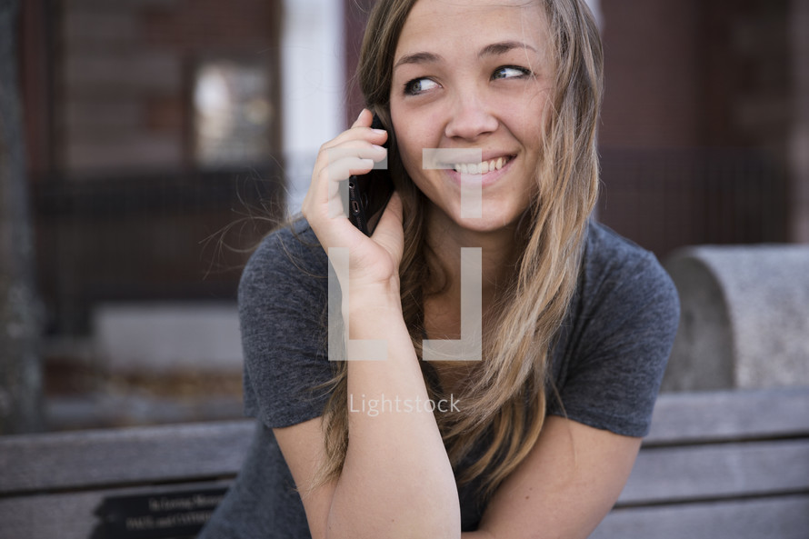 a young woman talking on the phone.