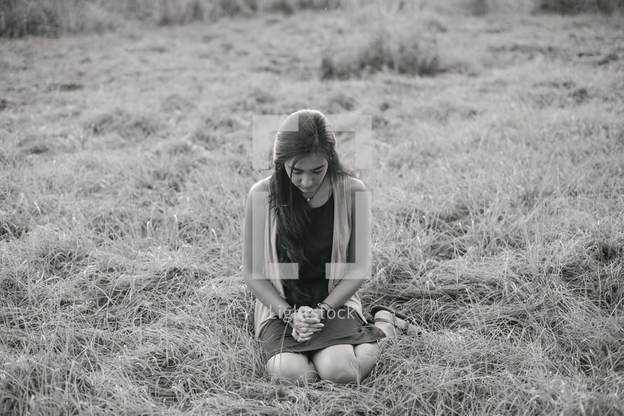 a woman kneeling in grass praying