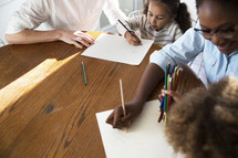 children coloring at the kitchen table with mom and dad