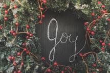 Joy written on a chalkboard inside a wreath