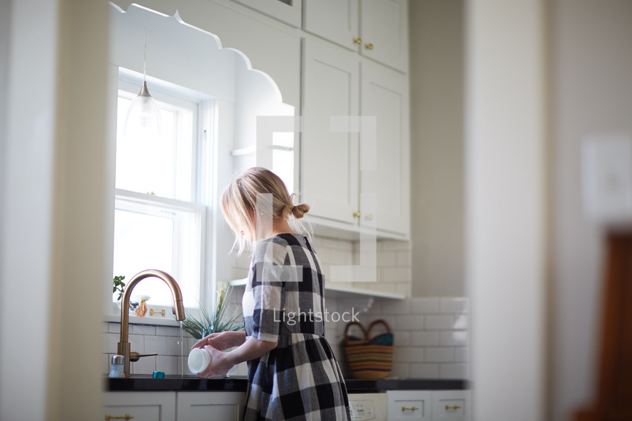 a woman in a kitchen washing dishes