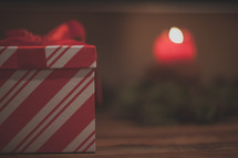 A red and white gift box and a candle