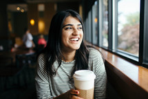 a smiling woman sitting in a window seat in a coffee shop holding a coffee