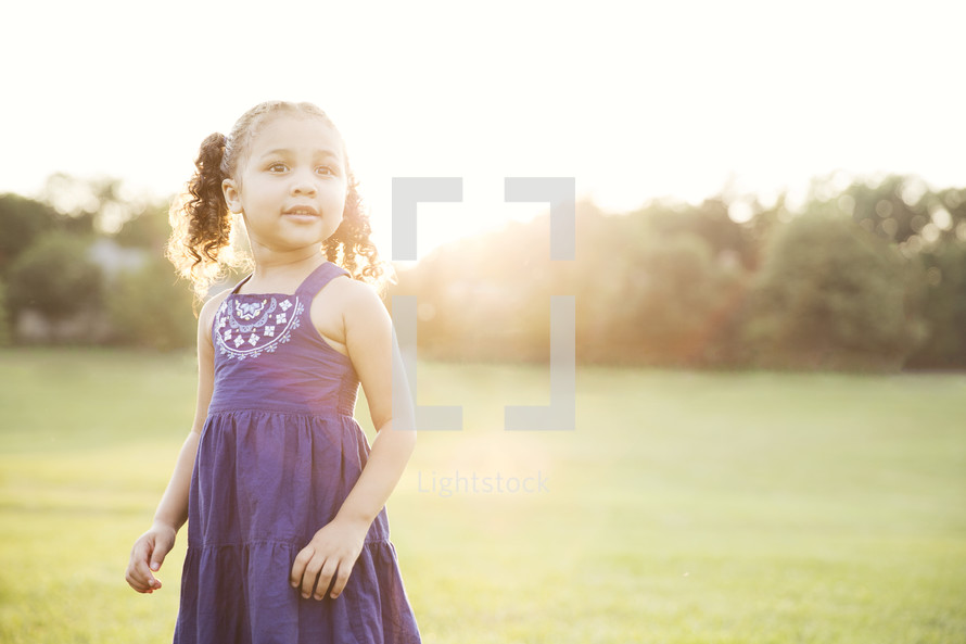 toddler girl standing outdoors enjoying summer