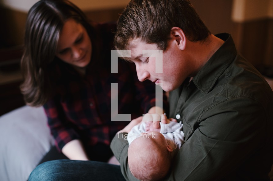 a mother and father holding a newborn baby