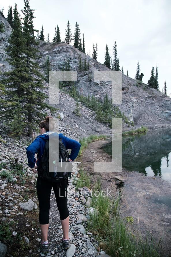 woman backpacking walking along the edge of a lake shore