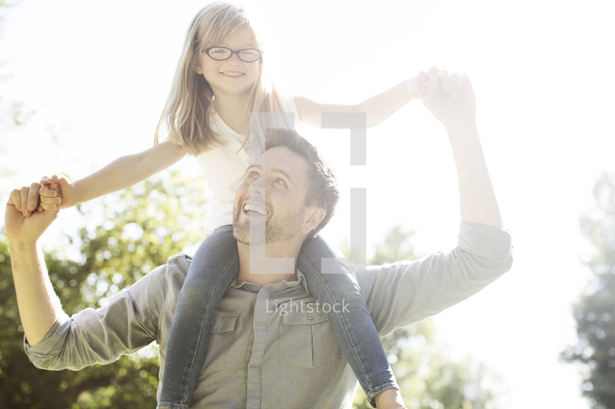 daughter riding on father's shoulders outdoors