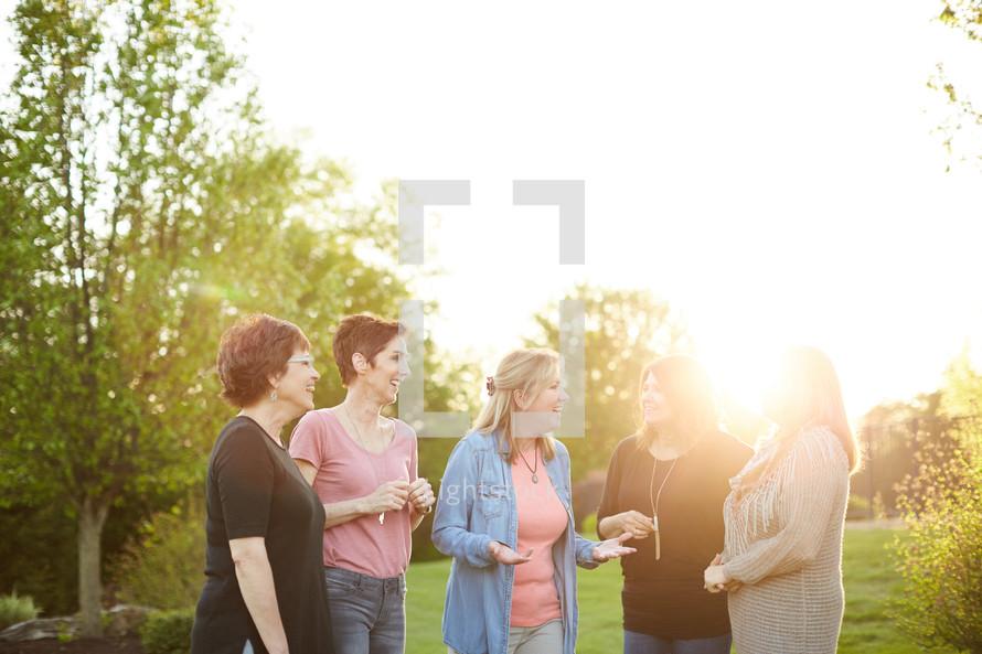 women standing in a backyard talking