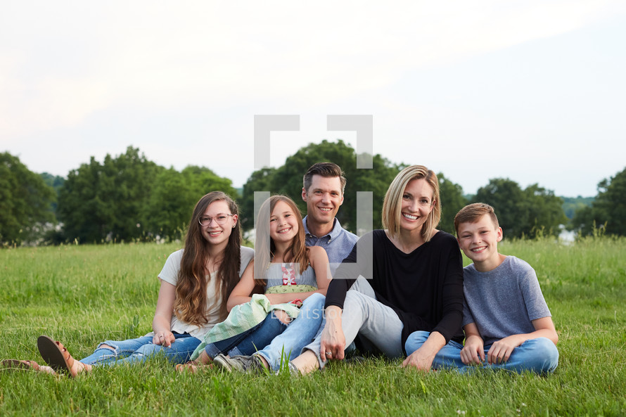 a family portrait sitting together in grass