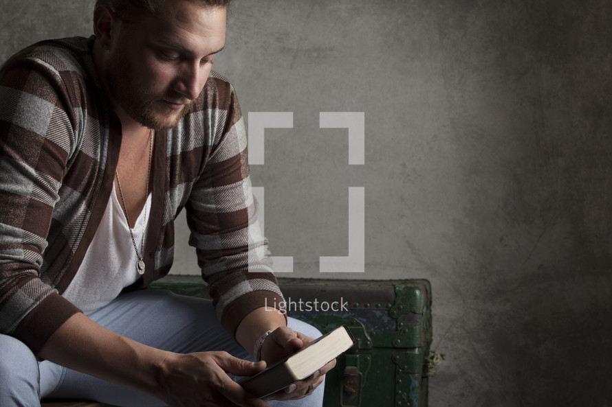 man holding a Bible sitting in thought