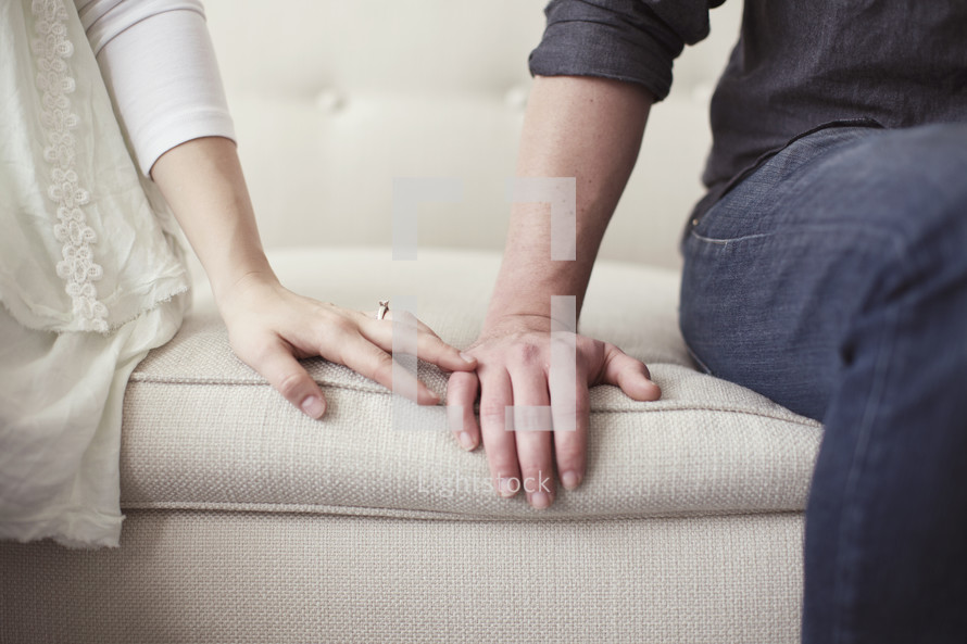 Closeup of husband and wife's hands trying to make up after an argument.
