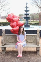 teen girl holding heart shaped red balloons