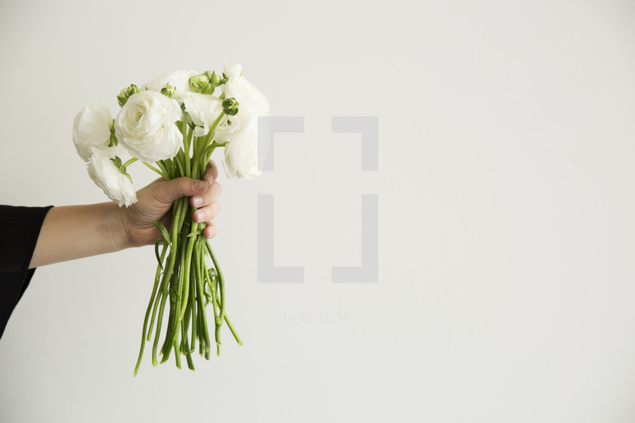 arm of a woman holding a bouquet of flowers